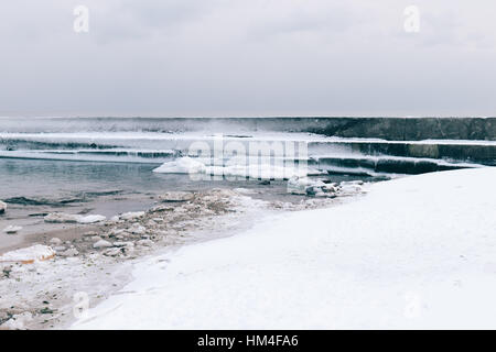 Views of ice-covered pier and snow on the beach, cloudy landscape - Stock Photo