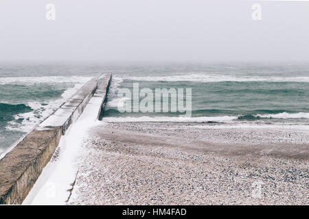 View of snow-covered pier and beach during blizzard, minimalist landscape, soft focus - Stock Photo