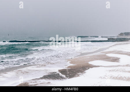 View of snow-covered pier and the sea during a snowfall in winter, soft focus - Stock Photo
