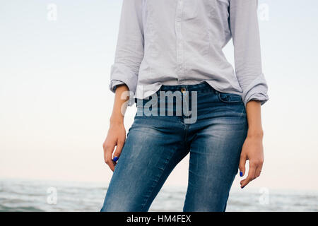 Details of women's clothing. A woman in a striped shirt and blue jeans standing on sea background. - Stock Photo