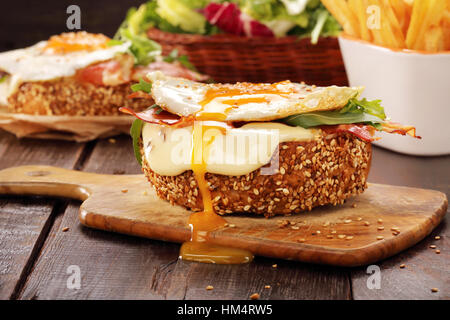 Sandwich with cheese bacon and fried egg on wooden background - Stock Photo