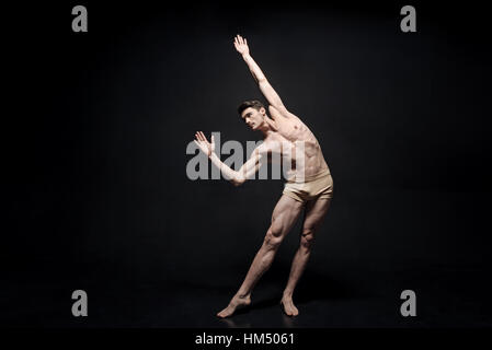 Masterful young dancer performing in the black colored studio - Stock Photo