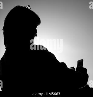 Silhouette of a woman taking a selfie. London, United Kingdom - Stock Photo