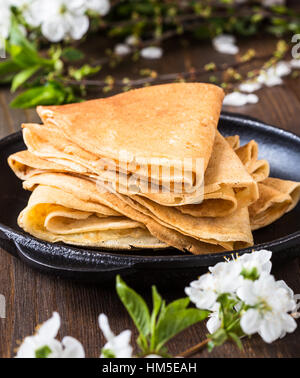Homemade crepes  folded in triangles on frying pan on spring blossom background - Stock Photo
