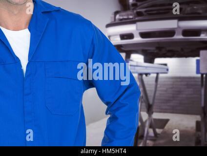 Mechanic standing at garage - Stock Photo