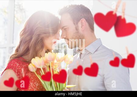 Couple embracing each other with red hanging hearts - Stock Photo