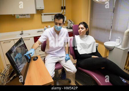 Dentist explaining x-ray report on desktop computer to patient while sitting in clinic - Stock Photo