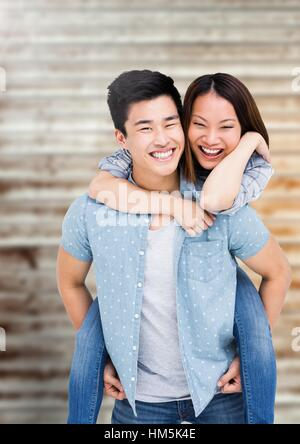 Happy man giving piggy back to woman - Stock Photo