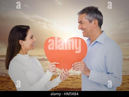 Composite image of couple holding red heart on beach - Stock Photo
