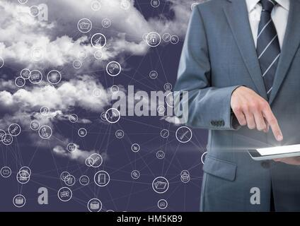 Businessman using digital tablet with connecting icons against blue background with clouds - Stock Photo