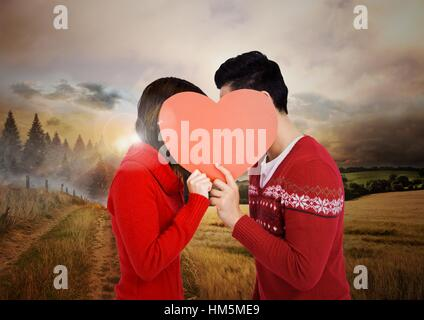 Couple holding heart against country scene - Stock Photo