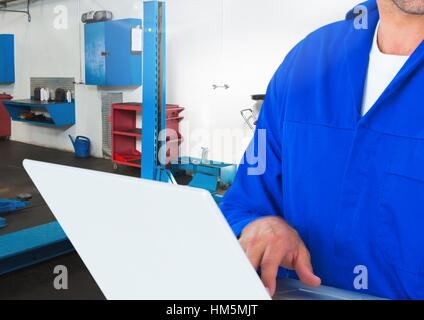 Mid section of mechanic using laptop - Stock Photo