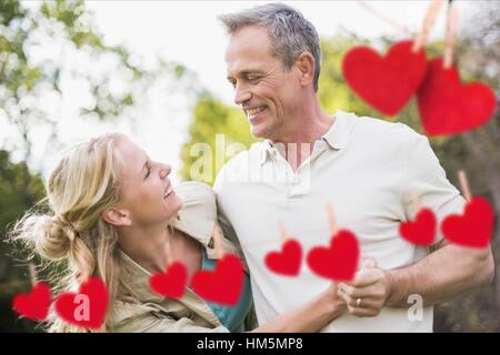 Couple having fun with red hanging hearts - Stock Photo