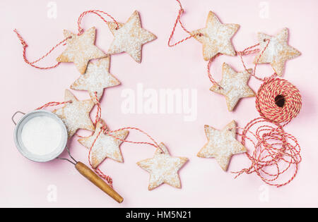 Christmas gingerbread star shaped cookies with sugar powder in sieve - Stock Photo