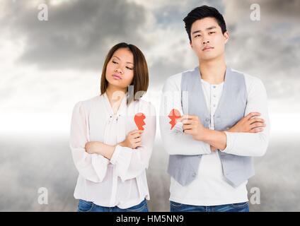 Depressed couple holding broken heart - Stock Photo