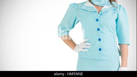 Air hostess in uniform standing with hand on hip - Stock Photo