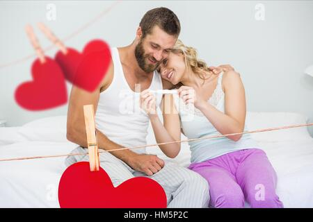 Romantic couple looking at pregnancy test in bedroom at home - Stock Photo