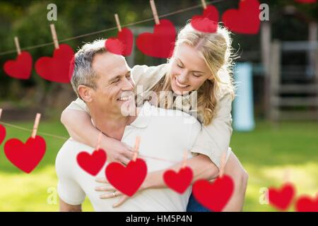Composite image of red hanging heart and man giving a piggyback to woman - Stock Photo