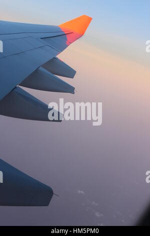 View through airliner window high above clouds at sunset - Stock Photo