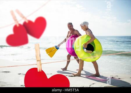 Senior couple with swim ring and swimfin walking on beach - Stock Photo