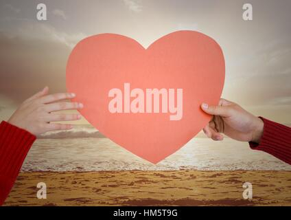 Hand of couple holding red heart on beach - Stock Photo