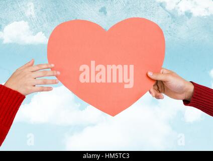 Composite image of hands holding a pink heart - Stock Photo