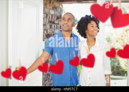 Composite image of red hanging hearts and couple entering home - Stock Photo
