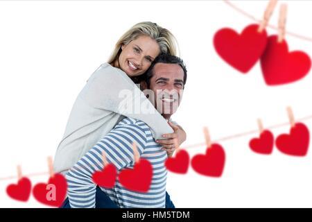 Happy man giving piggyback to woman - Stock Photo