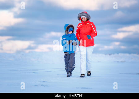 Cute little boy and his mother on icy beach - Stock Photo