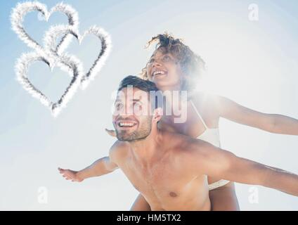 Composite image of man giving piggy back to woman - Stock Photo