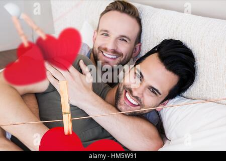 Homosexual couple embracing each other in bedroom at home - Stock Photo