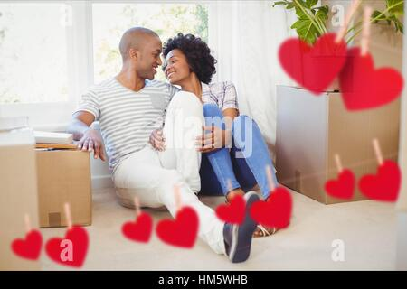 Couple embracing in living room at home against hearts hanging on a line - Stock Photo