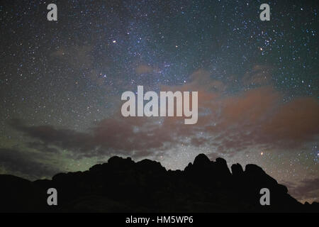 Scenic view of silhouette rock formation against star field at night - Stock Photo