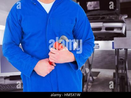 Mid section of mechanic holding pipe wrench - Stock Photo