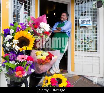 Portrait of male florist standing in doorway of flower shop - Stock Photo