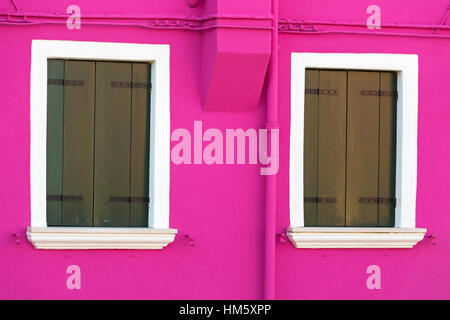 Closed window shutters against brightly coloured purple pink wall of house at Burano - Bright colors of Burano, - Stock Photo