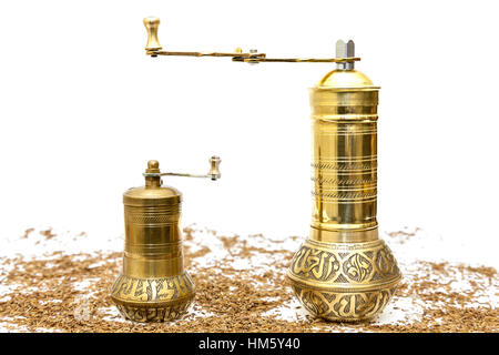 Large and small spice grinders with whole cumin seeds (jeera) on a white background - Stock Photo