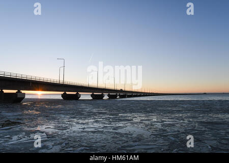 Ice floe and sunset by the Oland bridge connecting the island Oland with mainland Sweden - Stock Photo
