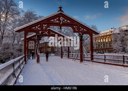 Gamle bybro, the old town bridge over the river Nid in Trondheim, Norway. The view is seen in Winter with blue sky. - Stock Photo