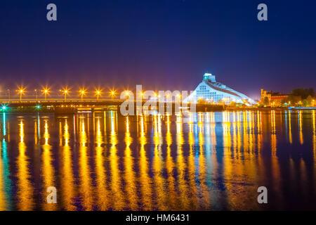 Bright bridge and night reflections in Daugava river. Modern National Library of Latvia in Riga - Stock Photo