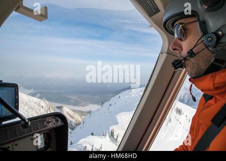 Helicopter pilot flying over Esplanade Range; sub-range of Selkirk Range; British Columbia; Canada - Stock Photo