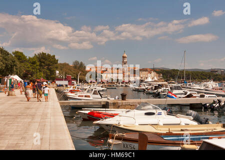 KRK, CROATIA - AUGUST 11: Tourists walk along marina and seafront of mediterranean town of island Krk on August - Stock Photo