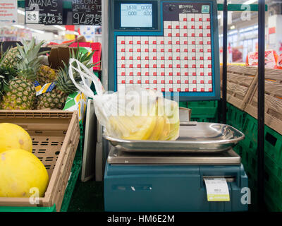 Weighting bananas at the Carrefour Market store, Cremona, Italy - Stock Photo