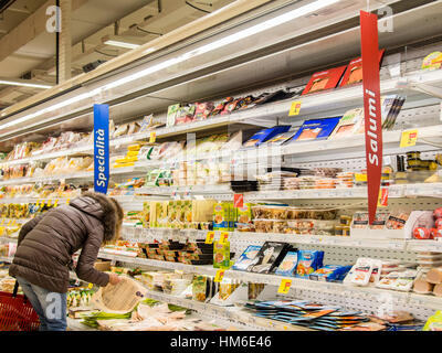 Woman shopping at the Carrefour Market store, Cremona, Italy. Different products in a refrigerator - Stock Photo