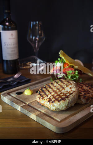 Grilled chicken burger on wooden board with wine bottle and glass - Stock Photo