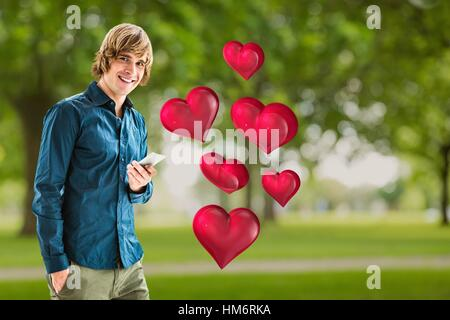 Smiling man holding mobile phone against digitally generated red hearts - Stock Photo