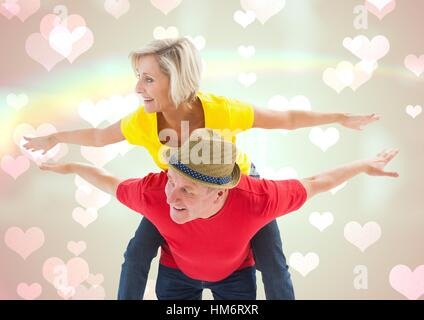Mature man giving piggy back to woman - Stock Photo