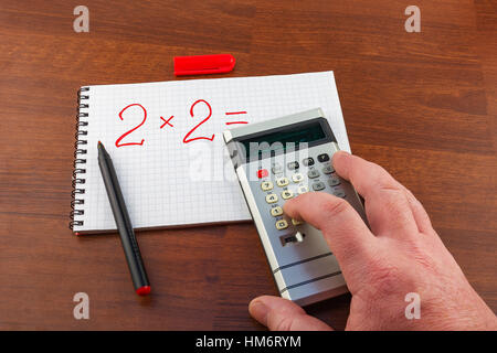 Man's hand pushes the button on the calculator solving the equation - Stock Photo