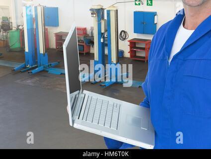 Mechanic using laptop in workshop - Stock Photo