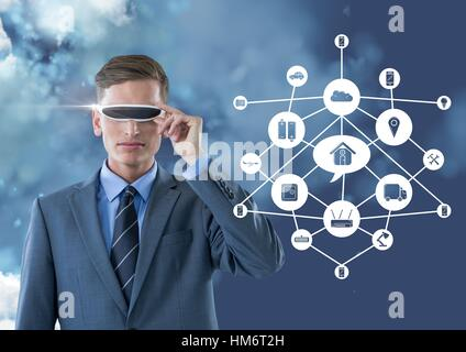 Business man wearing vr glasses standing next to digitally generated connecting icons - Stock Photo